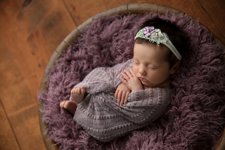 newborn girl posed in purple on brown wood
