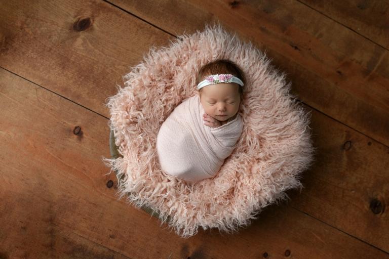 newborn girl in pink bowl on brown wood floor