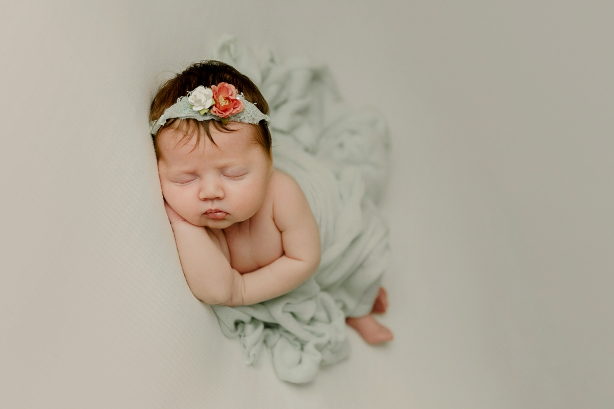 newborn baby girl in mint pink and white