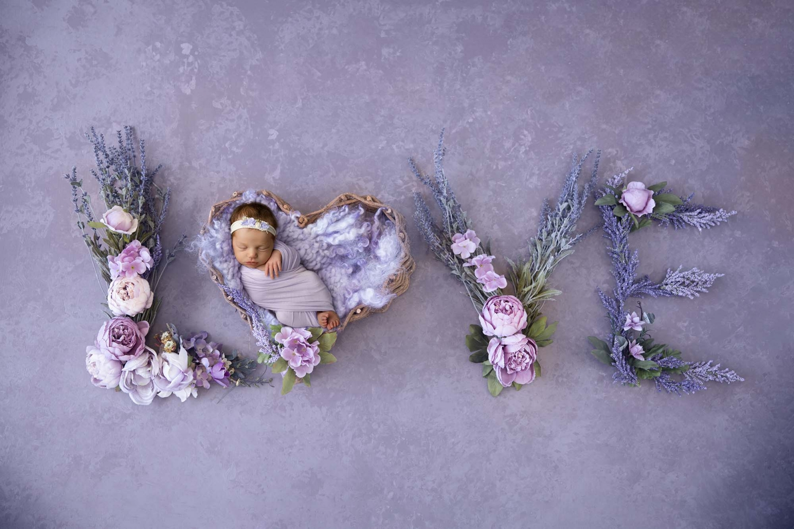 composite newborn photography with purple flowers in letters love