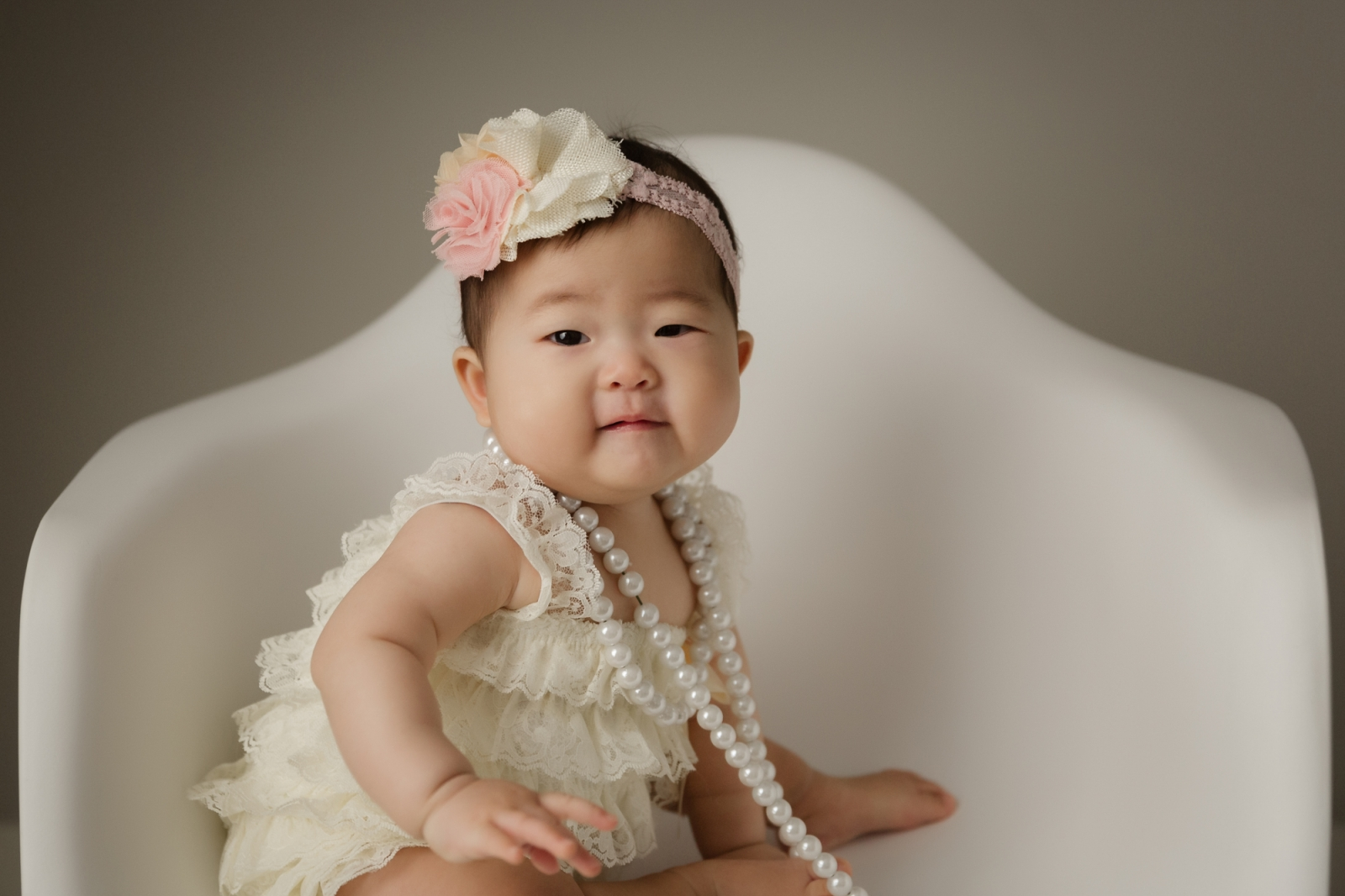 6 month old baby girl sitting in white chair in the studio